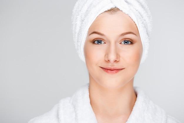 Asciugamano di bagno abbastanza biondo dell'involucro della donna sopra capelli bagnati