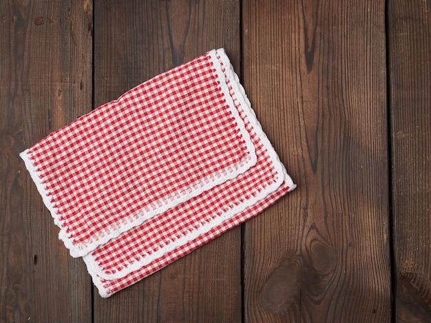 Asciugamano di cucina a quadretti bianco e rosso su una tavola di legno marrone