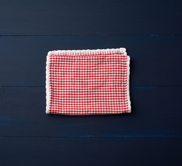 Asciugamano di cucina a quadretti rosso bianco su un blu di legno