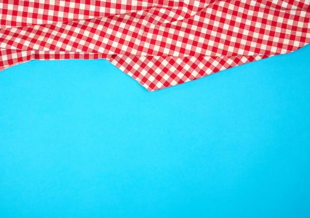 Asciugamano di cucina a quadretti rosso bianco su un fondo blu, fondo luminoso di picnic