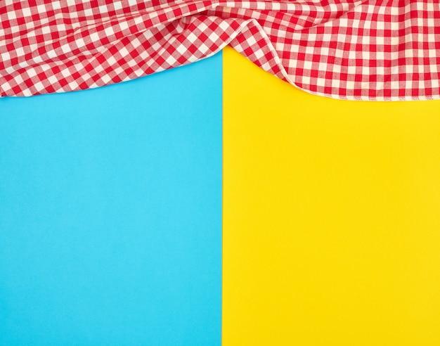 Asciugamano di cucina a quadretti rosso bianco su un fondo giallo blu