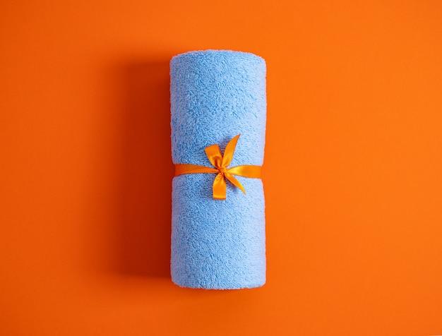 Asciugamano di spugna blu arrotolato legato da nastro contro uno sfondo arancione. vista dall'alto.