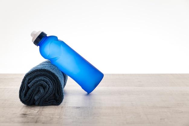Asciugamano e bottiglia con acqua per allenamento in palestra