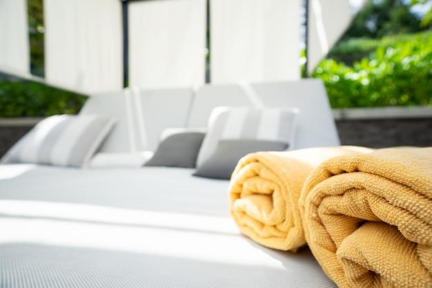 Asciugamano giallo piegato sul letto piscina presso la spa