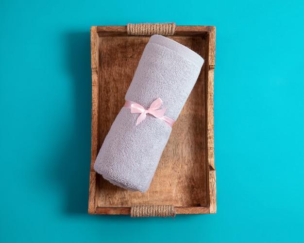 Asciugamano in spugna arrotolato da nastro rosa sul vassoio in legno in stile rustico