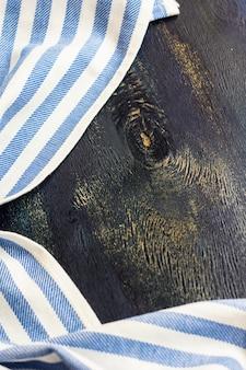Asciugamano o tovagliolo di cucina sopra i precedenti rustici della tavola