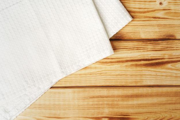 Asciugamano o tovagliolo di cucina sopra la tavola di legno.