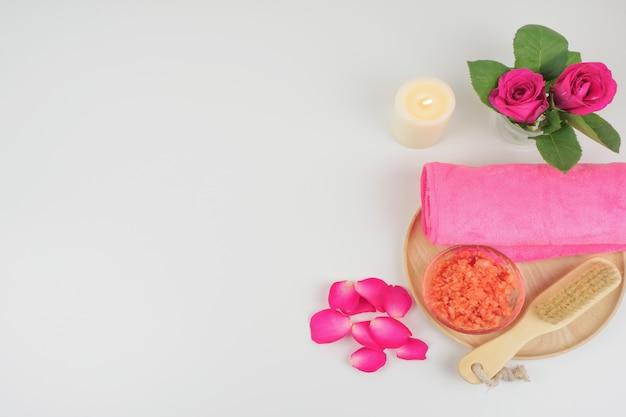 Asciugamano rosa e sale rosso con plumeria rosso sul piatto di legno