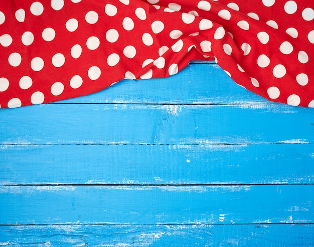 Asciugamano rosso del tessuto con i cerchi bianchi su un fondo di legno blu