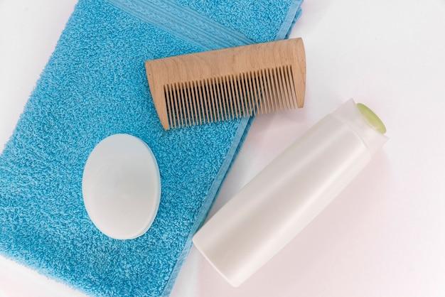 Asciugamano, sapone, shampoo e pettine su uno sfondo bianco.