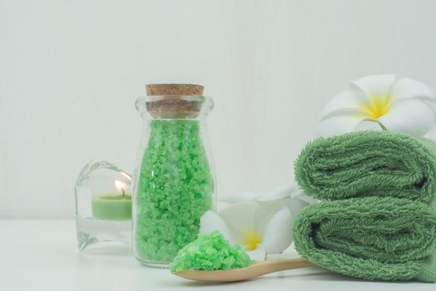 Asciugamano verde e sale di limone verde con plumeria rosso sul piatto di legno