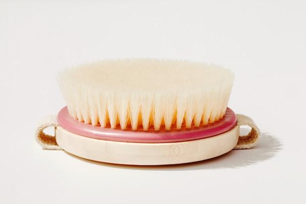Asciughi la spazzola di massaggio del corpo sulla parete bianca al giorno soleggiato. strumento per la pelle liscia e morbida.