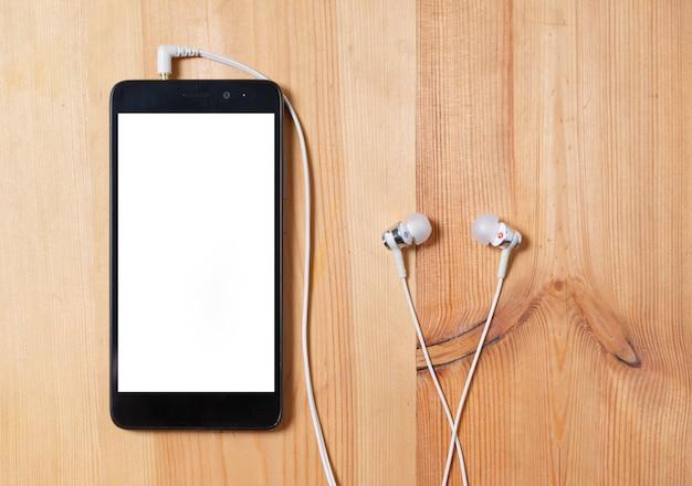 Ascoltare la musica. telefono verticale con custodia nera e uno schermo bianco bianco e cuffie con un orecchio sulla superficie di legno