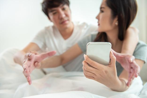 Ascoltare segretamente la conversazione al telefono o sbirciare post sociali, messaggi. il giovane asiatico e la donna litigano sul telefono cellulare intelligente con il concetto di relazione di argomento