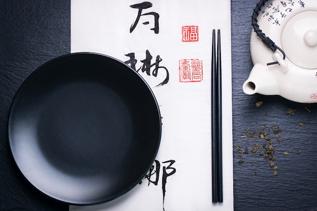 Asia composizione degli alimenti con le bacchette cinesi e piatto vuoto su un fondo di pietra scura