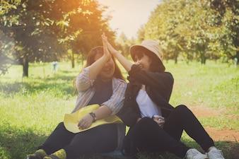 Asia donne, adolescenti, ragazze che si siedono nel giardino della frutta con relax e felice.
