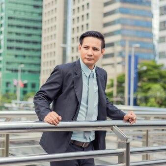 Asia giovane uomo d'affari di fronte al moderno edificio nel centro della città.
