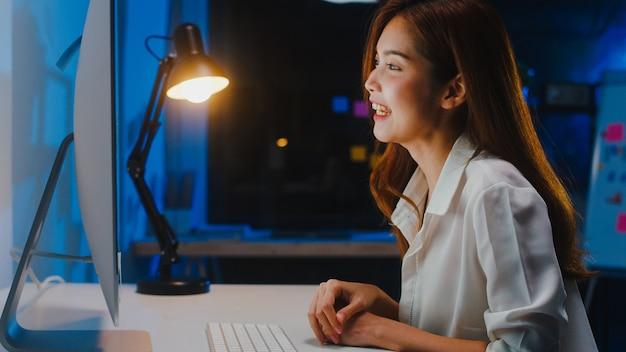 Asia imprenditrice utilizzando il computer parlare con i colleghi del piano in videochiamata mentre si lavora da casa in soggiorno di notte. autoisolamento, allontanamento sociale, quarantena per la prevenzione del coronavirus.