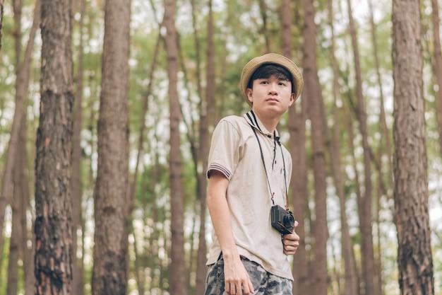 Asia uomo indossa camicia, cappello e pantaloni mimetici, cammina e scatta foto nella foresta