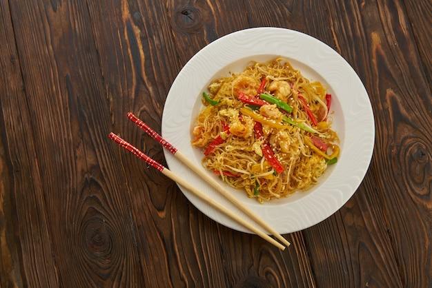 Asian deliziosi spaghetti saltati in padella con gamberi, verdure, peperoni rossi e bacchette su sfondo di legno spazio copia