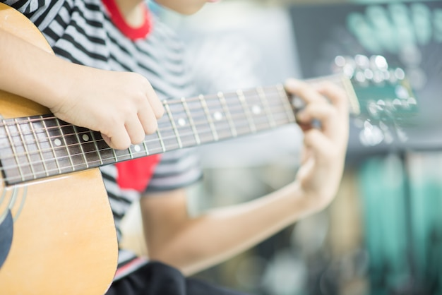 Asian girl studyguitar nell'aula di musica
