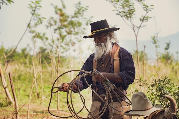 Asian man cowboy sta prendendo un vitello per essere marchiato in un ranch