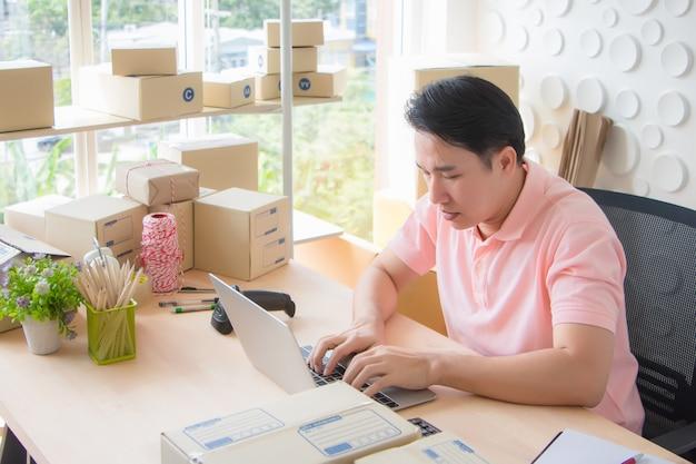 Asian thailand man digitando documenti su un computer portatile grave e spesso la repulsione sulla sua scrivania piena di attrezzature utilizzate per imballare la scatola e scansionare un codice a barre al mattino.