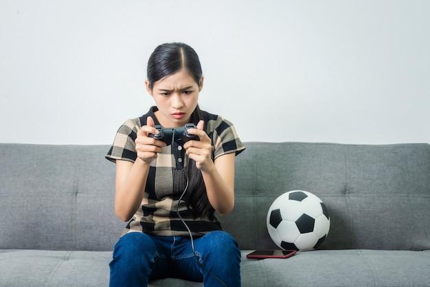 Asiatica della giovane donna infelice mentre giocando al videogioco dopo aver perso la missione, capelli neri.