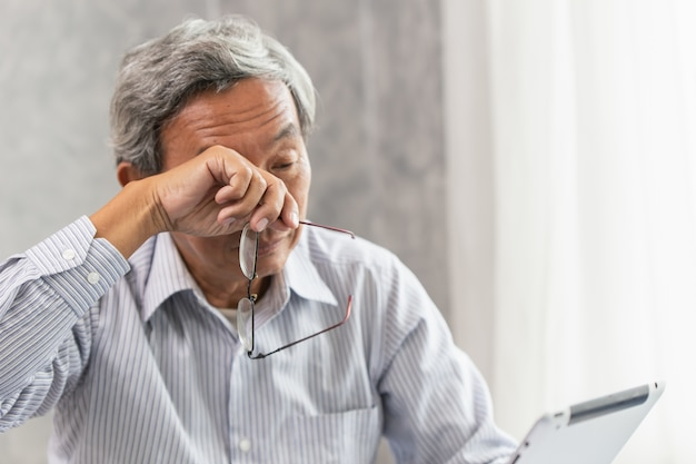 Asiatico anziano problema di irritazione degli occhi affaticamento e stanco dal duro lavoro o sindrome da visione del computer