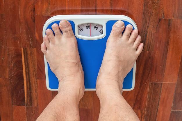 Asiatico che pesa sulla piattaforma di pesatura. è molto grasso
