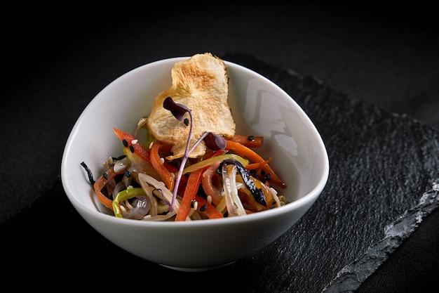 Asiatico con pasta di miso, salsa di soia, erbe aromatiche. su un tavolo di pietra nera, con le bacchette. copia vista dall'alto
