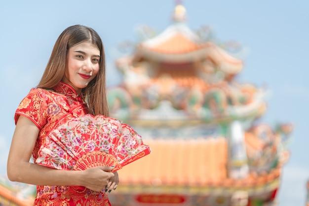Asiatico della bella donna che porta vestito rosso durante il nuovo anno cinese