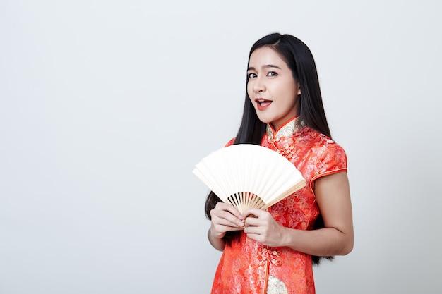 Asiatico della donna che porta vestito rosso durante il nuovo anno cinese