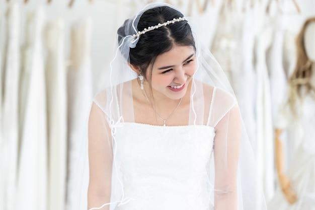 Asiatico della giovane donna che sorride e che prova sul vestito da sposa in un negozio.