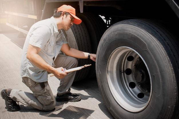 Asiatico un camionista che tiene appunti ispezionando controllo di sicurezza ruote di un camion.