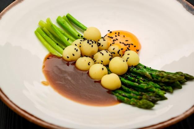 Asparagi con patate novelle, con ragù di carne e tuorlo d'uovo