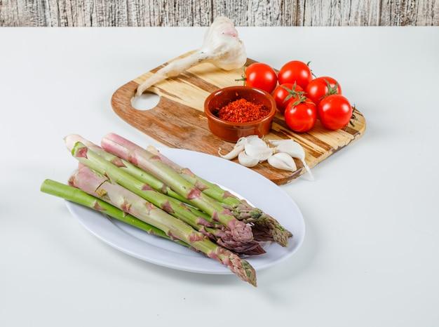 Asparagi con pomodori, aglio e peperoncino in polvere sul tagliere in un piatto bianco su superficie bianca