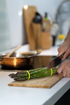 Asparagi freschi sulla cucina con la mano dell'uomo, chef che taglia gli asparagi.