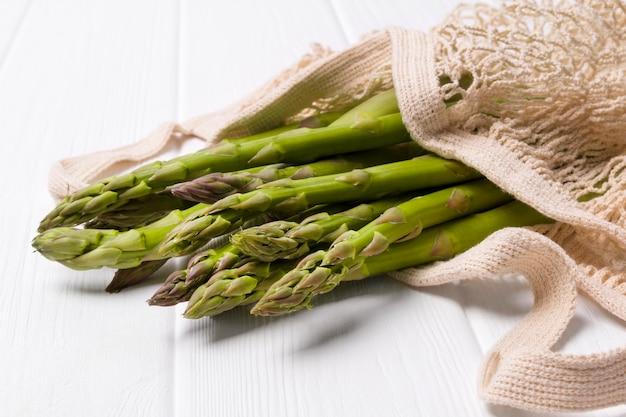 Asparagi verdi freschi nel sacchetto della spesa della corda sulla tavola di legno bianca della tavola