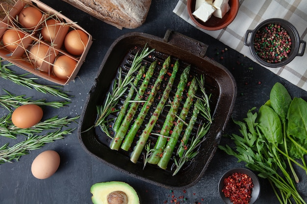 Asparagi verdi grigliati in una padella con ingredienti intorno. verdure, pane senza glutine, uova e prezzemolo. disteso. concetto di cibo sano