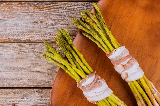 Asparago verde avvolto con pancetta sul piatto di legno.