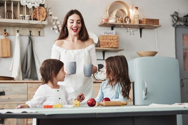 Aspettando le tazze. la giovane bella donna dà ai bambini le bevande mentre si siedono vicino al tavolo con i giocattoli
