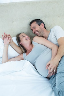 Aspettando una coppia sdraiata sul letto e chiacchierando nella loro camera da letto