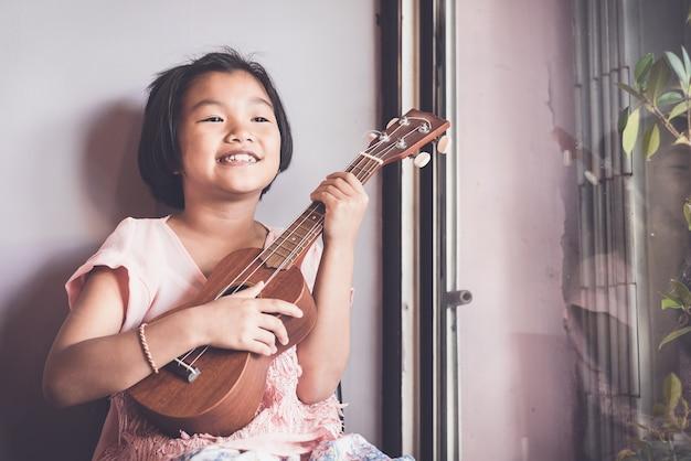 Aspetto ragazza asiatica da dieci anni a suonare ukulele tra studiare musica alla musica