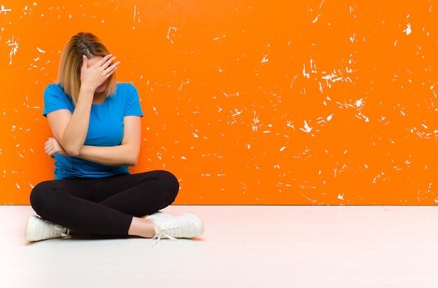Aspetto stressato, vergognoso o turbato, con mal di testa, coprendosi il viso con la mano