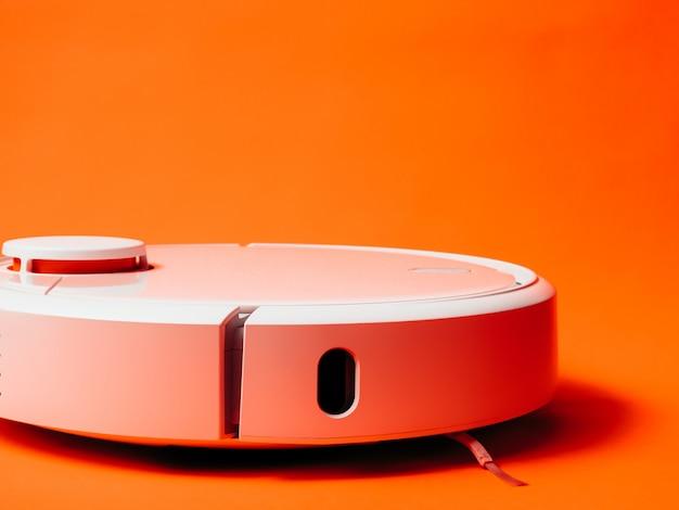 Aspirapolvere bianco del robot isolato su fondo arancio.