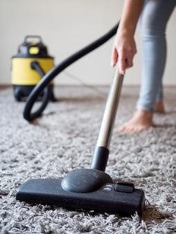 Aspirapolvere del primo piano che pulisce la moquette