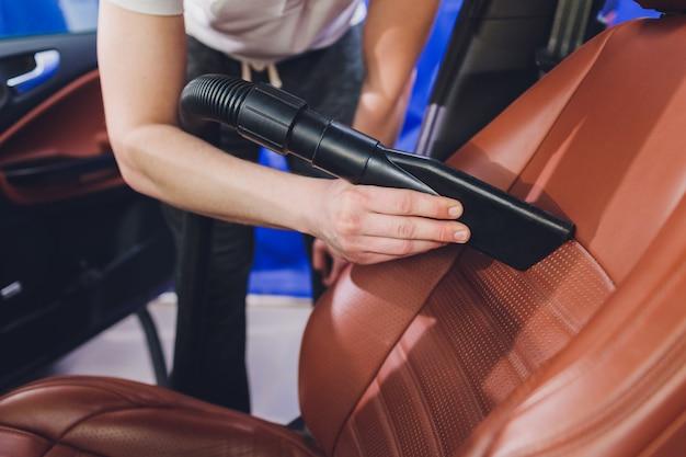 Aspirapolvere interno del veicolo. colpo del dettaglio di un aspirapolvere industriale che pulisce un seggiolino per auto.