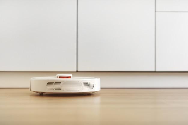 Aspirapolvere robot bianco. il robot è controllato da comandi vocali per la pulizia diretta. tecnologia moderna di pulizia intelligente. pulizia programmata dell'appartamento. messa a fuoco selettiva