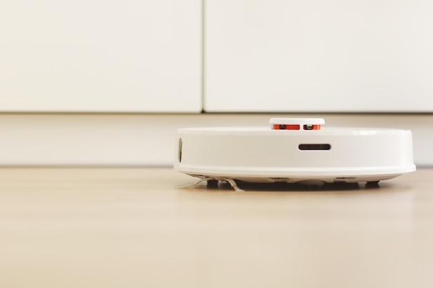 Aspirapolvere robot bianco. il robot è controllato da comandi vocali per la pulizia diretta.